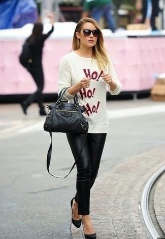Cómo combinar: jersey con cuello circular estampado en blanco y rojo, pantalones pitillo negros, zapatos de tacón de ante negros, bolso de hombre de cuero negro