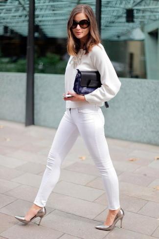 Cómo combinar: jersey con cuello circular blanco, vaqueros pitillo blancos, zapatos de tacón de cuero plateados, cartera sobre de pelo azul marino