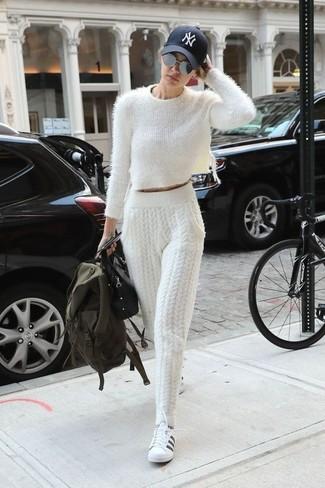 Look de Gigi Hadid: Jersey corto de angora blanco, Pantalón de chándal de punto blanco, Tenis de cuero en blanco y negro, Bolso de hombre de cuero negro