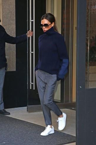 Look de Victoria Beckham: Jersey de cuello alto azul marino, Pantalón de pinzas gris, Tenis de cuero blancos