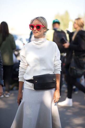 Elige una apariencia sofisticada en un jersey de cuello alto blanco y una falda midi de lana gris.