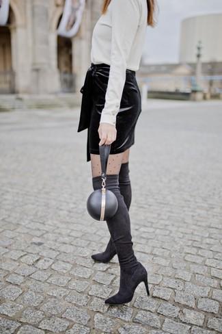 Cómo combinar: jersey de cuello alto blanco, minifalda de terciopelo negra, botas sobre la rodilla de ante negras, cartera sobre de cuero negra
