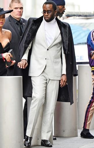 Cómo combinar: botines chelsea de cuero negros, jersey de cuello alto blanco, traje en beige, abrigo con cuello de piel negro