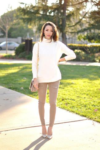 Cómo combinar: jersey de cuello alto de lana blanco, vaqueros pitillo marrón claro, zapatos de tacón de cuero blancos, bolso bandolera de cuero con print de serpiente marrón claro