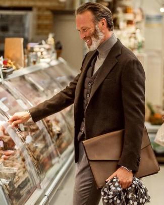 Combinar un portafolio de cuero marrón: Emparejar un chaleco de abrigo acolchado en gris oscuro junto a un portafolio de cuero marrón es una opción atractiva para el fin de semana.