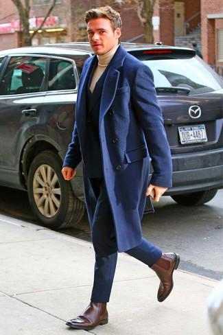 Cómo combinar: botines chelsea de cuero en marrón oscuro, jersey de cuello alto marrón claro, traje azul marino, abrigo largo azul marino