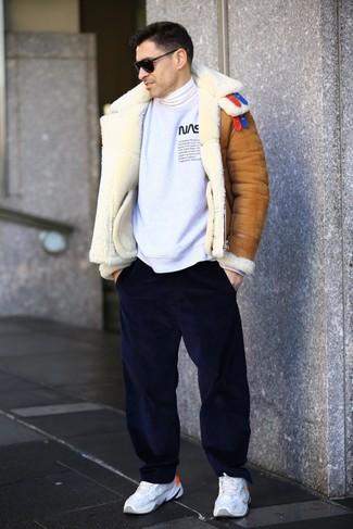 Cómo combinar: pantalón chino de pana azul marino, jersey de cuello alto blanco, sudadera estampada en blanco y negro, chaqueta de piel de oveja en tabaco