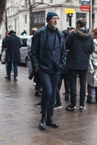 Moda para hombres de 40 años: Equípate un abrigo largo de tartán en azul marino y verde con un traje de rayas verticales azul marino para rebosar clase y sofisticación. Complementa tu atuendo con zapatos brogue de cuero negros.