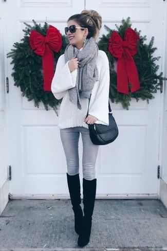 Cómo combinar: jersey de cuello alto de lana de punto blanco, vaqueros pitillo grises, botas de caña alta de ante negras, bolso bandolera de cuero negro