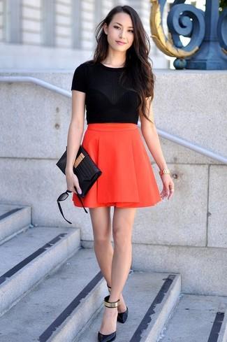Cómo combinar: jersey de manga corta negro, falda skater roja, zapatos de tacón de cuero en negro y dorado, cartera sobre de cuero negra