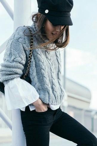 Cómo combinar: jersey de ochos de punto gris, blusa de manga larga con volante blanca, vaqueros pitillo negros, bolso bandolera de ante negro