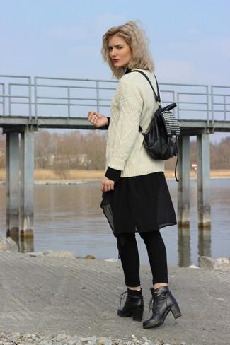 Un jersey de ochos beige y unos vaqueros pitillo negros son el combo perfecto para llamar la atención por una buena razón. Con el calzado, sé más clásico y opta por un par de botines con cordones de cuero negros.