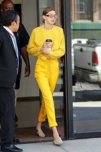 Look de Gigi Hadid: Jersey oversized amarillo, Pantalones pitillo amarillos, Chinelas de cuero en beige, Gafas de sol doradas