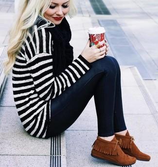 Este combinación de un jersey oversized de rayas horizontales blanco y negro y unos vaqueros pitillo negros te da una onda muy informal y accesible. Complementa tu atuendo con botas safari.
