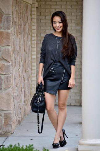 Opta por un jersey oversized de punto gris oscuro y una minifalda de cuero negra para un look agradable de fin de semana. Luce este conjunto con zapatos de tacón de cuero negros.