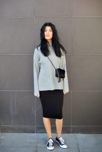 Este combo de un jersey oversized de punto gris oscuro y una falda midi negra te permitirá mantener un estilo cuando no estés trabajando limpio y simple. ¿Quieres elegir un zapato informal? Elige un par de tenis de lona en negro y blanco para el día.