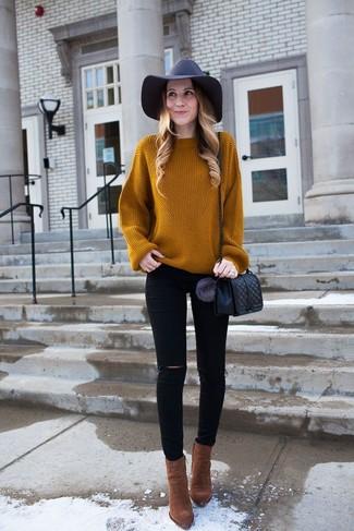 Un jersey oversized de punto en tabaco y unos vaqueros pitillo desgastados negros de mujeres de Saint Laurent son una opción excelente para el fin de semana. Dale onda a tu ropa con botines de ante marrónes.
