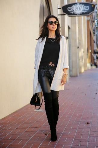 Cómo combinar: botas sobre la rodilla de ante negras, leggings de cuero negros, camiseta con cuello circular de encaje negra, cárdigan abierto de punto blanco