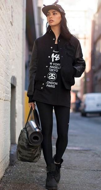 Cómo combinar: botas planas con cordones de ante negras, leggings negros, camiseta con cuello circular estampada en negro y blanco, chaqueta varsity negra