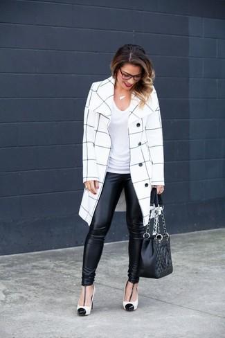 Cómo combinar: zapatos de tacón de cuero en blanco y negro, leggings de cuero negros, camiseta con cuello en v blanca, abrigo a cuadros en blanco y negro