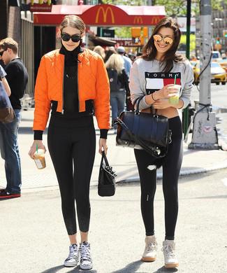 Cómo combinar: zapatillas altas de lona en negro y blanco, leggings negros, camiseta de manga larga de malla negra, cazadora de aviador naranja
