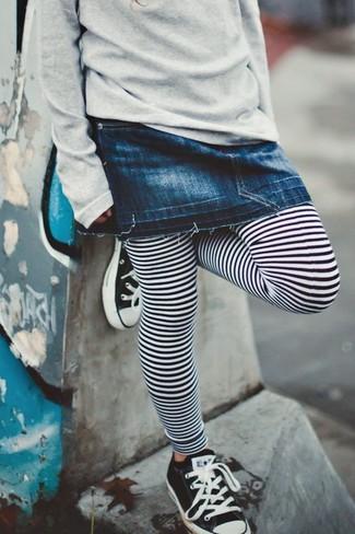 Cómo combinar: zapatillas en negro y blanco, leggings de rayas horizontales en blanco y negro, falda vaquera azul marino, jersey gris