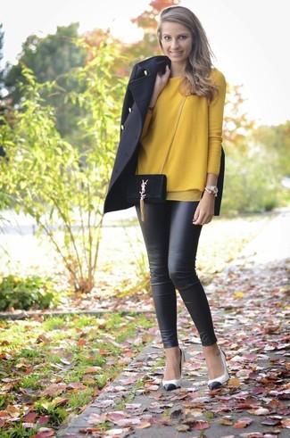 Cómo combinar: zapatos de tacón de cuero en blanco y negro, leggings de cuero negros, jersey con cuello circular mostaza, abrigo negro