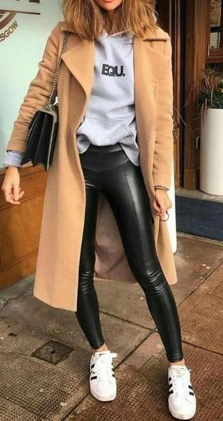Cómo combinar: tenis de cuero en blanco y negro, leggings de cuero negros, sudadera con capucha estampada gris, abrigo marrón claro
