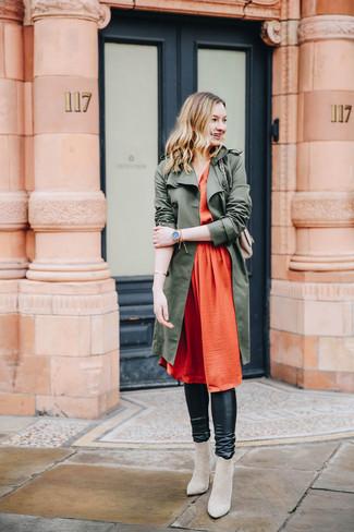 Cómo combinar: botines de ante en beige, leggings de cuero negros, vestido midi de seda plisado naranja, gabardina verde oliva