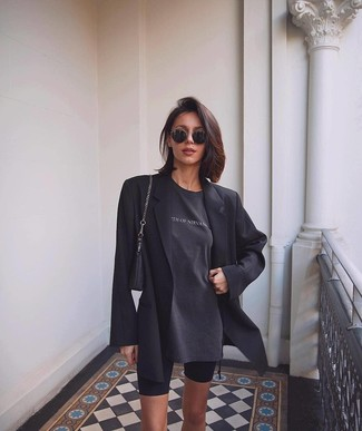 Cómo combinar: cartera de cuero negra, mallas ciclistas negras, camiseta con cuello circular estampada en gris oscuro, blazer negro