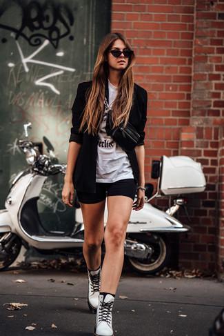 Cómo combinar: botas planas con cordones de cuero blancas, mallas ciclistas negras, camiseta con cuello circular estampada en blanco y negro, blazer negro