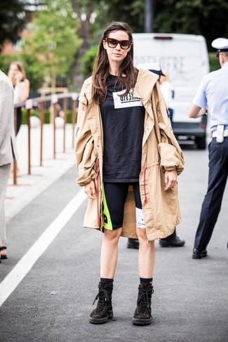 Cómo combinar: botas planas con cordones de ante en marrón oscuro, mallas ciclistas estampadas negras, camiseta con cuello circular estampada en negro y blanco, gabardina marrón claro