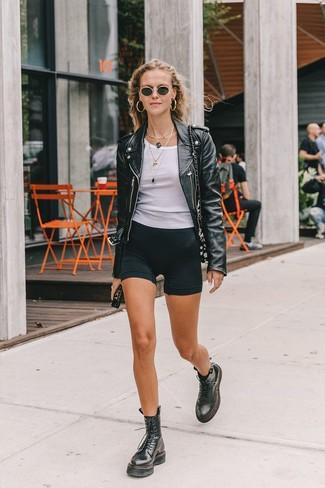 Cómo combinar: botas planas con cordones de cuero negras, mallas ciclistas negras, camiseta sin manga blanca, chaqueta motera de cuero negra
