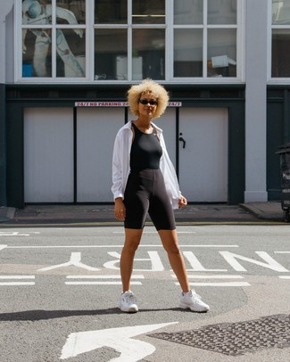 Cómo combinar: deportivas blancas, mallas ciclistas negras, camiseta sin manga negra, chubasquero blanco