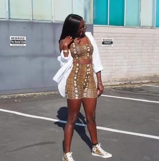 Cómo combinar: zapatillas altas de cuero doradas, mallas ciclistas con print de serpiente marrónes, top corto con print de serpiente marrón, camisa de vestir blanca