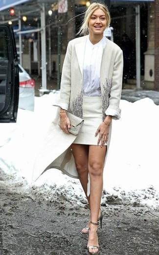 Cómo combinar: sandalias de tacón de cuero doradas, minifalda en beige, blusa de botones blanca, abrigo en beige