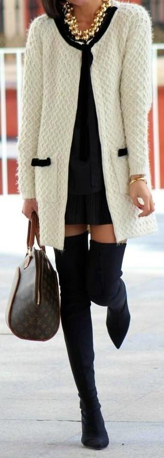 Cómo combinar: botas sobre la rodilla de ante negras, minifalda plisada negra, blusa de manga larga negra, cárdigan abierto de punto blanco