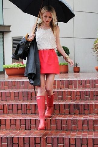Cómo combinar: botas de lluvia rojas, minifalda roja, blusa sin mangas de encaje blanca, gabardina negra