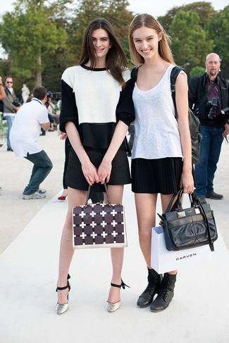Cómo combinar: zapatos de tacón de cuero con print de serpiente grises, minifalda acolchada negra, blusa sin mangas de gasa negra, jersey corto en blanco y negro