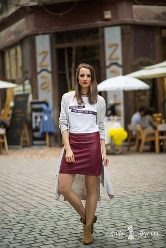Cómo combinar: botines de ante marrónes, minifalda de cuero burdeos, camiseta con cuello circular estampada en blanco y negro, cárdigan abierto gris