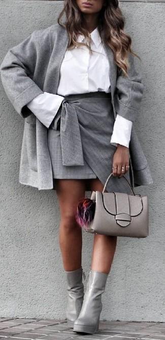 Cómo combinar: botines de cuero grises, minifalda con recorte gris, camisa de vestir blanca, abrigo gris