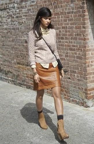 Combinar una minifalda de cuero marrón: Opta por un jersey de ochos en beige y una minifalda de cuero marrón para un almuerzo en domingo con amigos. Botines de ante marrón claro son una opción práctica para complementar tu atuendo.