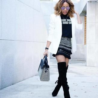 Cómo combinar: botas sobre la rodilla de ante negras, minifalda de lana negra, camiseta con cuello circular estampada en negro y blanco, blazer blanco