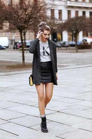 Cómo combinar: botas planas con cordones de cuero negras, minifalda de cuero negra, camiseta con cuello circular estampada gris, blazer en gris oscuro