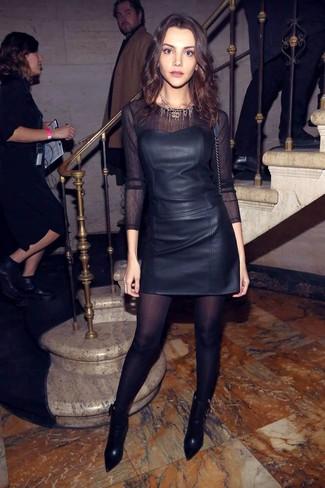 Cómo combinar: botines de cuero negros, minifalda de cuero negra, camiseta de manga larga de malla negra, corsé de cuero negro