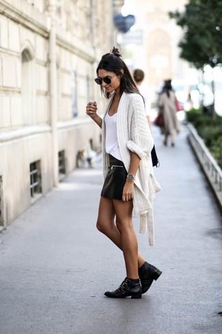 Cómo combinar: botines de cuero con tachuelas negros, minifalda de cuero negra, camiseta sin manga blanca, cárdigan abierto de punto blanco