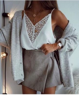 Cómo combinar: colgante dorado, minifalda de ante gris, camiseta sin manga de encaje blanca, cárdigan gris