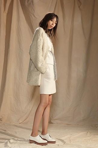 Cómo combinar: zapatos oxford de cuero blancos, minifalda de punto blanca, jersey con cuello circular blanco, abrigo de forro polar en beige