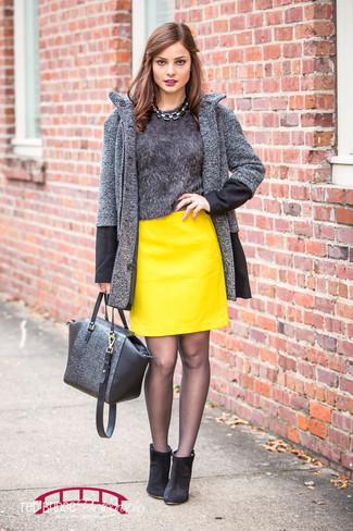 Cómo combinar: botines de ante negros, minifalda de cuero amarilla, jersey con cuello circular de angora en gris oscuro, abrigo de espiguilla en gris oscuro