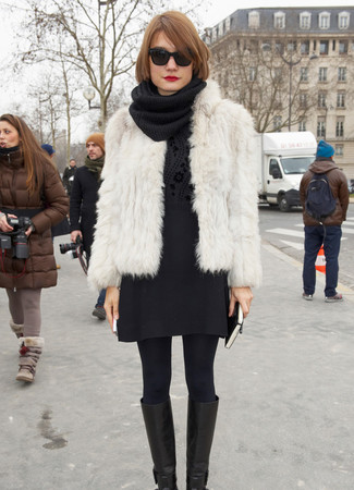 Cómo combinar: botas de caña alta de cuero negras, minifalda de lana negra, jersey con cuello circular con print de flores negro, chaqueta de piel blanca